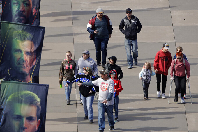 Fans walk past banners of drivers as they arrive for a NASCAR Cup Series auto race at Kansas Speedway in, Kansas City, Kan. Sunday, Oct. 20, 2019. (AP Photo/Charlie Riedel)