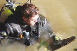 In this recent photo, muddy waters make it difficult to see subsurface structures, so divers like Maxwell Faulkner have to feel around with their hands to check for cracks and other degradation during underwater inspections near Columbus, Ohio. That sometimes means pulling objects to the surface for a closer look. (Marc Kovac/The Columbus Dispatch via AP)