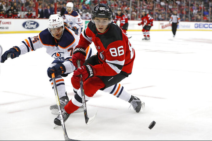 Edmonton Oilers defenseman Ethan Bear (74) defends New Jersey Devils center Jack Hughes (86) during the second period of an NHL hockey game Thursday, Oct. 10, 2019, in Newark, N.J. (AP Photo/Kathy Willens)
