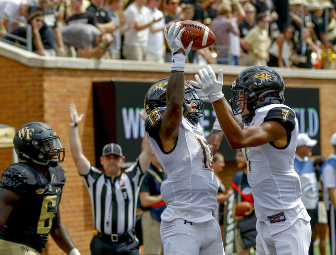 Towson running back Shane Simpson, left, celebrates with teammate Jabari Greenwood as Wake Forest defensive lineman Chris Calhoun looks on after Simpson scored a touchdown in the first half of a NCAA college football game in Winston-Salem, N.C., Saturday, Sept. 8, 2018. (AP Photo/Nell Redmond)