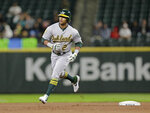 FILE - In this Sept. 24, 2018, file photo Oakland Athletics' Khris Davis rounds the bases after hitting a home run against the Seattle Mariners during a baseball game, in Seattle. Davis, last season's major league home run leader, has reached agreement with the  Athletics on a one-year contract to avoid salary arbitration. The A's also said Friday, Jan. 11, 2019, they had agreed to one-year deals with left-hander Sean Manaea, infielders Jurickson Profar and Marcus Semien and outfielder Mark Canha to avoid arbitration. (AP Photo/John Froschauer,File)