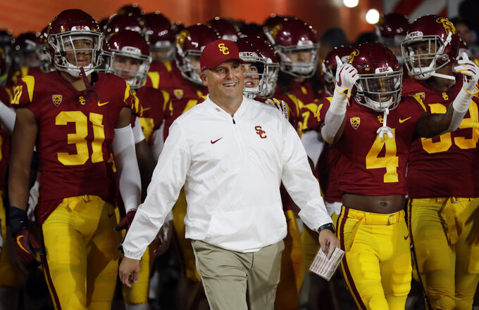 FILE - In this Oct. 13, 2018, file photo, Southern California head coach Clay Helton smiles as he enters the field with his team during an NCAA college football game against Colorado in Los Angeles. Saturday's game between USC and Oregon State will feature two contrasting teams. The Trojans are coming off a disheartening loss at home, while the Beavers had a statement-making win on the road. USC coach Clay Helton will try to get the Trojans back on track by taking over the play calling. (AP Photo/Marcio Jose Sanchez, File)