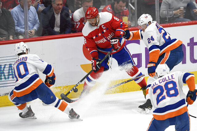 Washington Capitals left wing Alex Ovechkin (8), of Russia, and New York Islanders defenseman Scott Mayfield (24), left wing Michael Dal Colle (28) and Derick Brassard battle for the puck during the second period of an NHL hockey game, Monday, Feb. 10, 2020, in Washington. (AP Photo/Nick Wass)