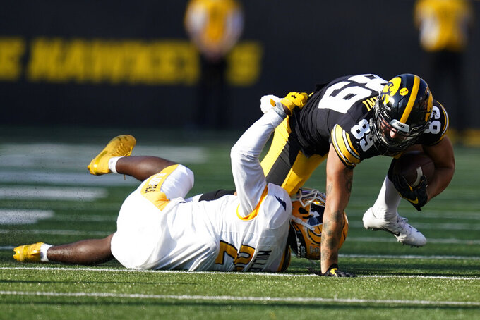Iowa wide receiver Nico Ragaini (89) is tackled by Kent State cornerback Montre Miller (21) after catching a pass during the second half of an NCAA college football game, Saturday, Sept. 18, 2021, in Iowa City, Iowa. Iowa won 30-7. (AP Photo/Charlie Neibergall)