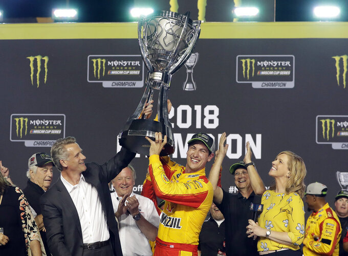 Joey Logano holds the trophy after winning the NASCAR Cup Series Championship auto race at the Homestead-Miami Speedway, Sunday, Nov. 18, 2018, in Homestead, Fla. (AP Photo/Lynne Sladky)