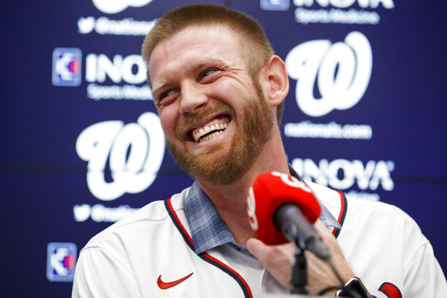 FILR - In this Dec. 17, 2019, file photo, Washington Nationals pitcher Stephen Strasburg smiles during a baseball media availability at Nationals Park in Washington. The  Nationals head to spring training with mostly the same squad that won the World Series. They are counting again on being led by a star-studded rotation featuring Max Scherzer and Strasburg, along with slugger Juan Soto.(AP Photo/Alex Brandon, File)