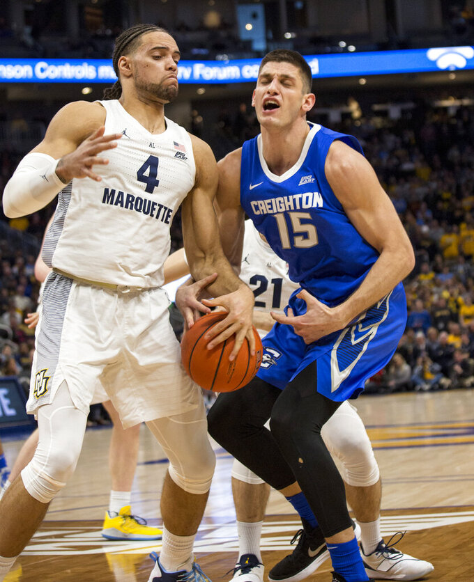 Creighton forward Martin Krampelj, right, and Marquette forward Theo John, left, battle for the ball during the second half of an NCAA college basketball game Sunday, March 3, 2019, in Milwaukee. (AP Photo/Darren Hauck)