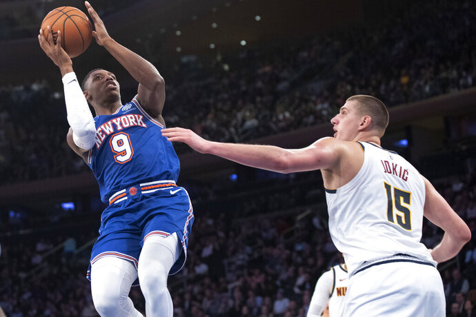 New York Knicks forward RJ Barrett (9) shoots next to Denver Nuggets center Nikola Jokic (15) during the second half of an NBA basketball game Thursday, Dec. 5, 2019, at Madison Square Garden in New York. (AP Photo/Mary Altaffer)