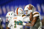 Miami quarterback D'Eriq King (1) celebrates with tight end Brevin Jordan (11) after they connected for a touchdown pass against Duke during the first quarter of an NCAA college football game Saturday, Dec. 5, 2020, in Durham, N.C. (Nell Redmond/Pool Photo via AP)