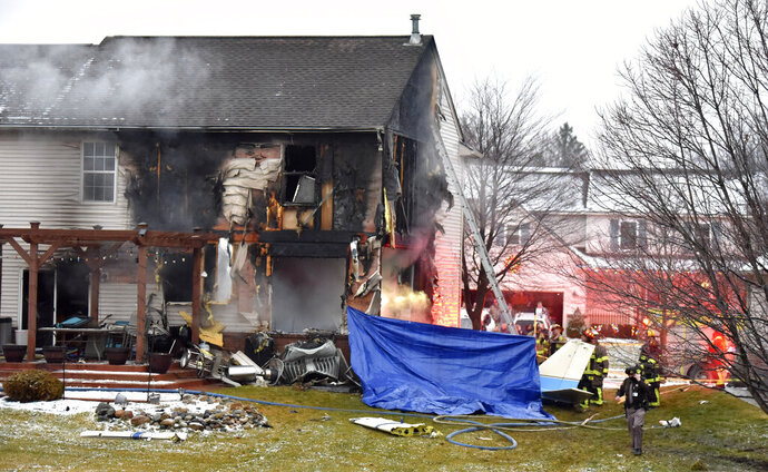 First responders investigate the scene of a plane that crashed into or near a house, setting the house on fire, on Dakota Dr. between Grispen Rd. and Cedar Mill Dr. in Lyon Twp. near the Oakland Southwest Airport, Saturday night, Jan. 2, 2021. (Todd McInturf/Detroit News via AP)