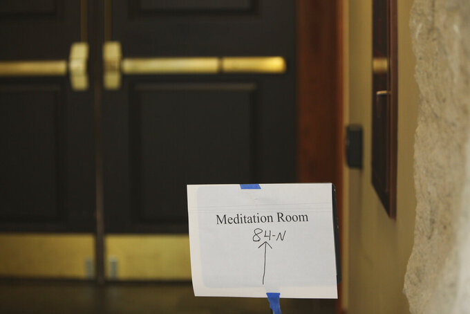 This Friday, May 28, 2021 photo shows a sign directing visitors to a meditation room through double doors to a hallway in the basement of the Kansas Statehouse in Topeka, Kan. The room once was located on the second floor, but Democratic Gov. Laura Kelly moved it to the basement to create more space for her staff, and the room's location has become a point of dispute between her and Republican lawmakers. (AP Photo/John Hanna)