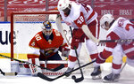 Florida Panthers goaltender Chris Driedger (60) looks to clear the puck as Detroit Red Wings right wing Givani Smith (48) closes in during the third period of an NHL hockey game Thursday, April 1, 2021, in Sunrise, Fla. (AP Photo/Jim Rassol)