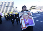 A mourner with a portrait of the deceased Kim Bok-dong, one of the former South Korean sex slaves who were forced to serve for the Japanese military in World War II, marches toward the Japanese Embassy during her funeral ceremony in Seoul, South Korea, Friday, Feb. 1, 2019. Hundreds of mourners gathered Friday near the Japanese Embassy in Seoul for the funeral of the South Korean woman forced as a girl into a brothel and sexually enslaved by the Japanese military in WWII. (AP Photo/Ahn Young-joon)