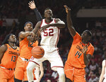 Oklahoma forward Kur Kuath (52) takes a foul as he goes up for a shot over Oklahoma St forward Cameron McGriff (12) and Yor Anei (14) during the second half of an NCAA college basketball game in Norman, Okla., Saturday, Feb. 1, 2020. (AP Photo/Kyle Phillips)