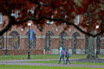 Christopher Newport University students make their way through campus as snow falls, Tuesday afternoon, Nov. 12, 2019 in Newport News, Va. (Jonathon Gruenke/The Virginian-Pilot via AP)