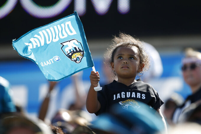 A Jacksonville Jaguars fan waves a flag during the second half of an NFL football game against the Arizona Cardinals, Sunday, Sept. 26, 2021, in Jacksonville, Fla. (AP Photo/Stephen B. Morton)