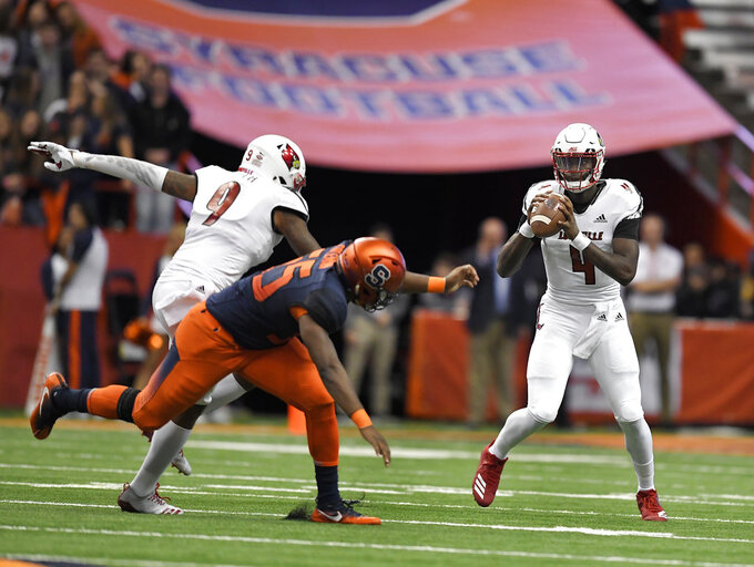 Louisville quarterback Jawon Pass, right, looks to pass as wide receiver Jaylen Smith, left, blocks against Syracuse defensive lineman Kendall Coleman during the first half of an NCAA college football game in Syracuse, N.Y., Friday, Nov. 9, 2018. (AP Photo/Adrian Kraus)