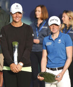 Sweden's AnnaNordqvist poses for the media holding the trophy after winning the Women's British Open golf championship, with Louise Duncan holding the leading amateur Scotland's Louise Duncan during the presentation ceremony in Carnoustie, Scotland, Sunday, Aug. 22, 2021. (AP Photo/Scott Heppell)