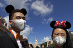 Visitors wearing face masks to prevent the spread of the new coronavirus, attend a reopening ceremony at the Hong Kong Disneyland on Thursday, June 18, 2020. Hong Kong Disneyland on Thursday opened its doors to visitors for the first time in nearly five months, at a reduced capacity and with social distancing measures in place. The theme park closed temporarily at the end of January due to the coronavirus outbreak, and is the second Disney-themed park to re-open worldwide, after Shanghai Disneyland. (AP Photo/Kin Cheung)