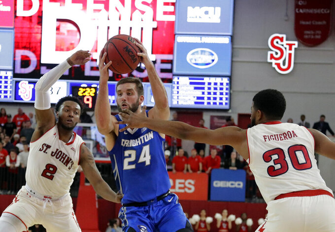 Creighton's Mitch Ballock (24) drives past St. John's LJ Figueroa (30) and Shamorie Ponds (2) during the first half of an NCAA college basketball game Wednesday, Jan. 16, 2019, in New York. (AP Photo/Frank Franklin II)