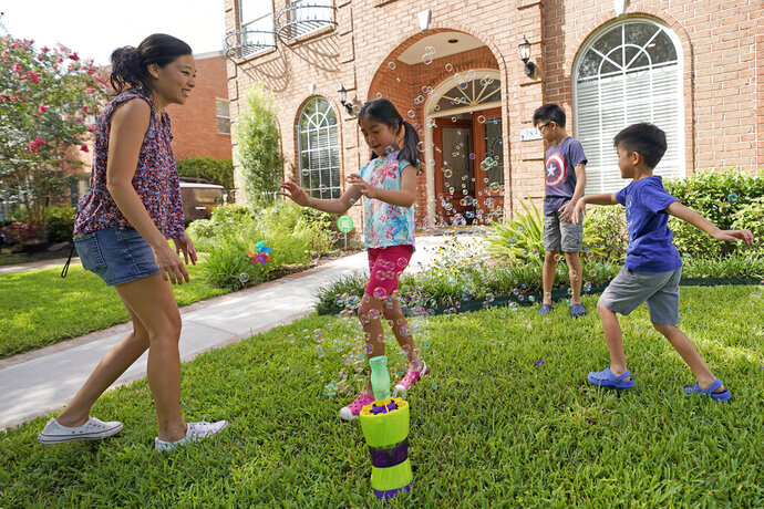 Vicky Li Yip, left, sets up a bubble machine for her children, left, to right, Kelsey, 8, Toby, 10 and Jesse, 5, outside their home, Friday, July 10, 2020, in Houston. Vicky Li Yip works from home and says online schooling has been exhausting, even with her husband helping out. But with her city becoming a national hot spot, she has been considering what it would mean for her children to face possible exposure every day. (AP Photo/David J. Phillip)