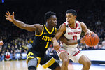 Wisconsin guard D'Mitrik Trice drives past Iowa guard Joe Toussaint, left, during the first half of an NCAA college basketball game, Monday, Jan. 27, 2020, in Iowa City, Iowa. (AP Photo/Charlie Neibergall)