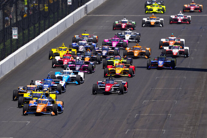 Scott Dixon of New Zealand leads the field into the first turn on the start the Indianapolis 500 auto race at Indianapolis Motor Speedway in Indianapolis, Sunday, May 30, 2021. Scott Dixon's perfect Indianapolis 500 fell apart when the six-time IndyCar Series champion ran out of gas before his first pit stop. (AP Photo/Paul Sancya)