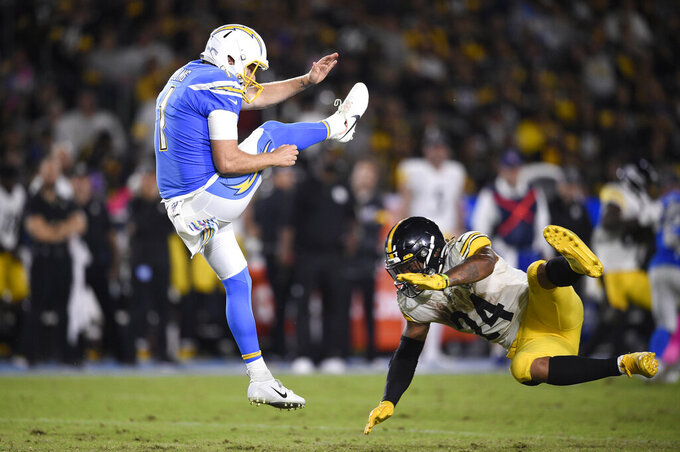 Los Angeles Chargers punter Ty Long, left, punts as Pittsburgh Steelers running back Benny Snell tries to block it during the second half of an NFL football game, Sunday, Oct. 13, 2019, in Carson, Calif. (AP Photo/Kelvin Kuo)