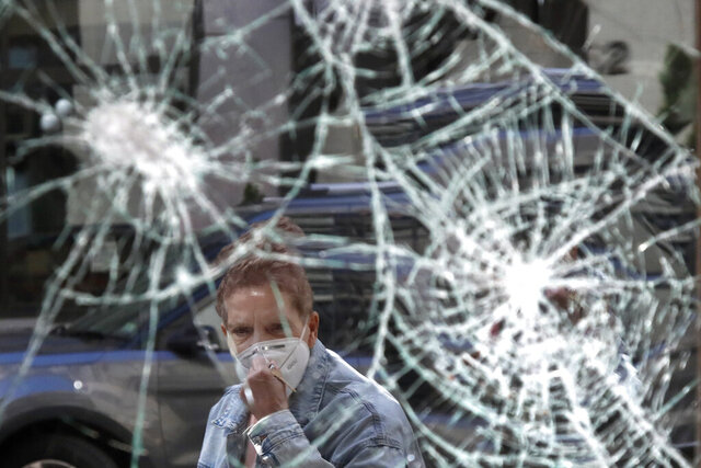 A woman wearing a mask due to coronavirus concerns, looks at a smashed storefront window in Boston's Downtown Crossing, Monday, June1, 2020. A march in Boston Sunday to protest the death of George Floyd, who died after being restrained by Minneapolis police officers on May 25, turned violent after dark. (AP Photo/Elise Amendola)