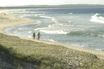 In this image made from a video, people walk along a beach in Tuncurry, Australia, Tuesday, May 18, 2021. A surfer was killed by a shark on Tuesday, police said. The man, aged in his 50s, had been surfing off Forster, 220 kilometers (137 miles) north of Sydney,  when he was attacked late in the morning, a police statement said. (Australian Broadcasting Corporation via AP)