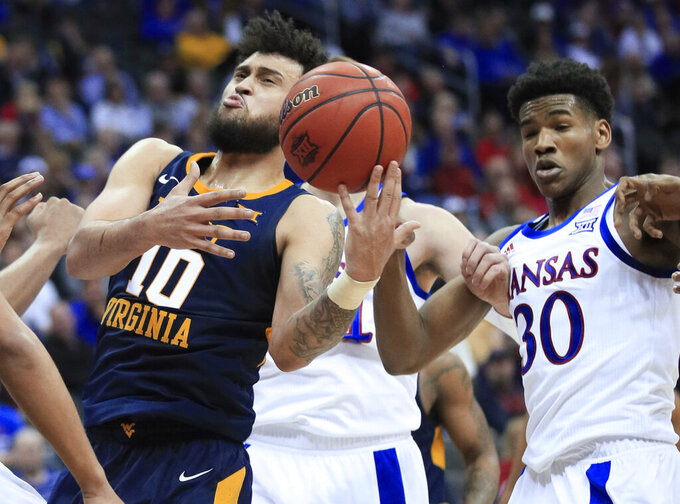 West Virginia guard Jermaine Haley (10) pulls in a rebound in front of Kansas guard Ochai Agbaji (30) during the second half of an NCAA college basketball game in the semifinals of the Big 12 men's tournament in Kansas City, Mo., Friday, March 15, 2019. Kansas won 88-74. (AP Photo/Orlin Wagner)