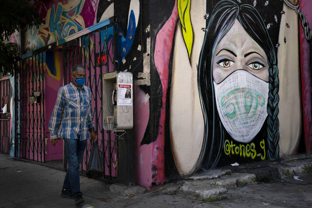 A man wearing a face mask walks past a mural Thursday, Oct. 1, 2020, in South Central Los Angeles. California's plan to safely reopen its economy will begin to require counties to bring down coronavirus infection rates in disadvantaged communities that have been harder hit by the pandemic. The complex new rules set in place an