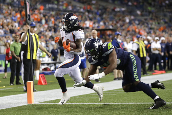 Denver Broncos running back Devontae Jackson, left, scores a touchdown ahead of Seattle Seahawks tight end Jacob Hollister during the second half of an NFL football preseason game Thursday, Aug. 8, 2019, in Seattle. (AP Photo/Stephen Brashear)