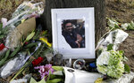 A photo tribute for Christchurch mosque shooting victim Syed Areeb Ahmed, 26, lies amid mounds of flowers in Christchurch, New Zealand on Tuesday, March 19, 2019. Ahmed's uncle described the Pakistani native as a bright accountant just starting his career who always put education first. (AP Photo/Mark Baker)