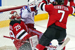 New York Rangers' Alexis Lafrenière, center, is pushed into New Jersey Devils goaltender Mackenzie Blackwood, left, after scoring a goal during the second period of the NHL hockey game in Newark, N.J., Sunday, April 18, 2021. (AP Photo/Seth Wenig)