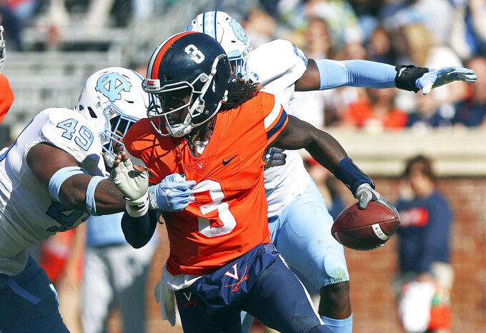 FILE - In this  Saturday, Oct. 27, 2018, file photo, Virginia's quarterback Bryce Perkins (3) scrambles away from two North Carolina defenders in the first half of an NCAA college football game in Charlottesville, Va. Pittsburgh faces Virginia on Friday. ( (Zack Wajsgras/The Daily Progress via AP, File)