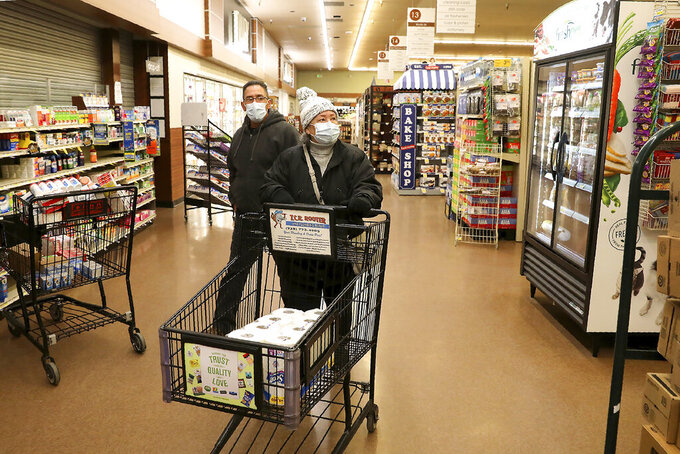 Hector Molina, left, helps his mother Gertrude Moore as the pair shop at the Safeway store in the University Plaza shopping center in Flagstaff, Ariz., at 6 a.m. Thursday morning, April 2, 2020. Some area stores have set aside special hours for seniors to shop to avoid exposure to the general public. (Jake Bacon/Arizona Daily Sun via AP)