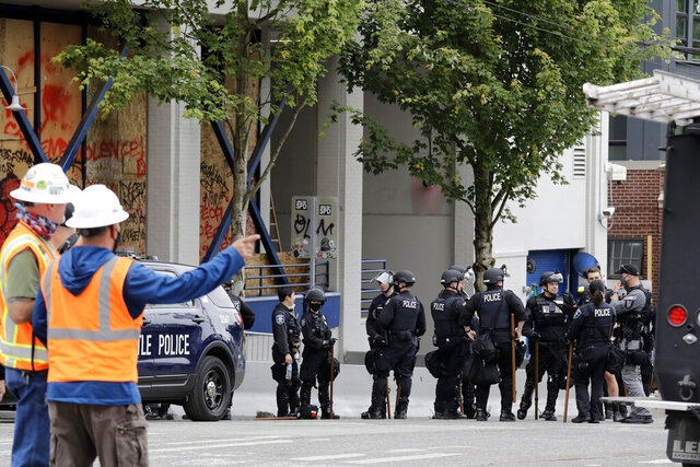 Police officers gather in front of a Seattle police precinct being cleaned and opened Wednesday, July 1, 2020, in Seattle, where streets had been blocked off in an area demonstrators had occupied for weeks. Seattle police showed up in force earlier in the day at the