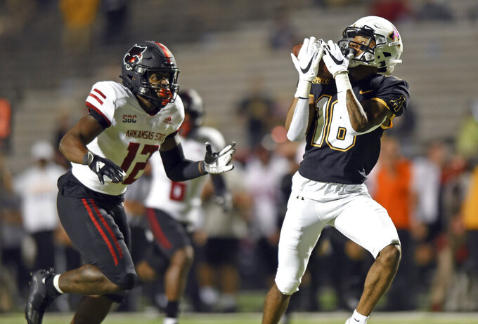 Appalachian State wide receiver Christian Wells, right, catches a touchdown pass ahead of Arkansas State linebacker C.J. Harrisin the first quarter of an NCAA college football game, Thursday, Oct. 22, 2020, at Kidd Brewer Stadium in Boone, N.C. (Walt Unks/Winston-Salem Journal via AP)