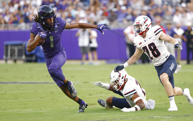 TCU wide receiver Quentin Johnston (1) catches a pass and runs for a first down as Duquesne defensive backs Leandro Debrito (7) and Spencer DeMedal (28) pursue during the first half of an NCAA college football game Saturday, Sept. 4, 2021, in Fort Worth, Texas. (AP Photo/Ron Jenkins)