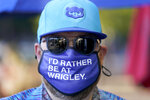 Patrick McCarron wears a Chicago Cubs cap and protective mask Friday, Sept. 4, 2020, as he heads to a rooftop venue to watch the Cubs host the rival St. Louis Cardinals at Wrigley Field in Chicago. The Cubs averaged 38,208 fans for their 81 home dates in 2019, trailing only the Los Angeles Dodgers, Cardinals and Yankees. Now those crowds are gone. (AP Photo/Charles Rex Arbogast)