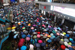 Demonstrators carry umbrellas as they march along a street in Hong Kong, Sunday, Aug. 18, 2019. Heavy rain fell on tens of thousands of umbrella-ready protesters as they started marching from a packed park in central Hong Kong, where mass pro-democracy demonstrations have become a regular weekend activity. (AP Photo/Vincent Yu)