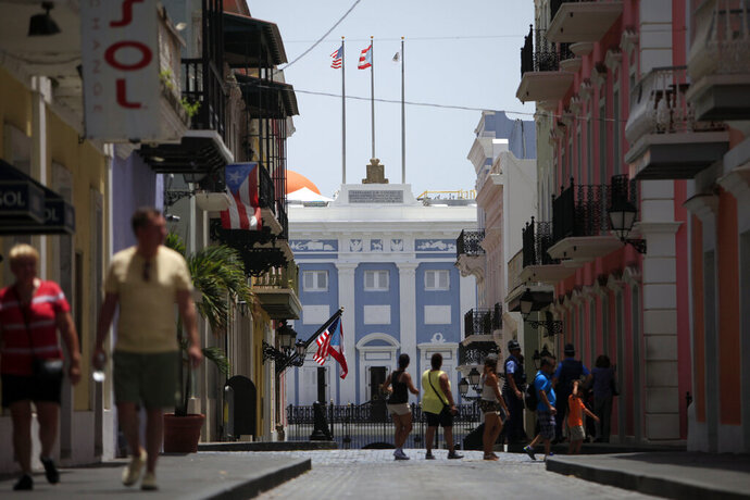 FILE - In this June 29, 2015 file photo, people walk on a street that leads to the baby blue governor's mansion known as the Palacio de Catalina, in Old San Juan, Puerto Rico. Officials said Friday, Nov. 22, 2019, crews are painting the historic governor's mansion to match its original color from the 16th century. (AP Photo/Ricardo Arduengo)