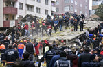 Rescue workers and people try to remove debris of an eight-story building which collapsed in Istanbul, Wednesday, Feb. 6, 2019. An eight-story building collapsed in Istanbul on Wednesday, killing at least one person and trapping several others inside the rubble, Turkish media reports said. (DHA via AP)