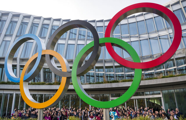 Young people pose behind the Olympic Rings during the Torch Tour ahead of the 2020 Winter Youth Olympic Games, front of the Olympic House, in Lausanne, Switzerland, Wednesday, Jan. 8, 2020. The 2020 Winter Youth Olympic Games take place in Lausanne from Jan. 9 to Jan. 22, 2020. (Jean-Christophe Bott/Keystone via AP)