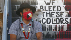 "Native American advocate Carl Moore sits near the phrase ""We Bleed These Colors"" along a walkway which leads from the Bountiful High School parking lot up to the football field Tuesday, July 28, 2020, in Bountiful, Utah. While advocates have made strides in getting Native American symbols and names changed in sports, they say there's still work to do mainly at the high school level, where mascots like Braves, Indians, Warriors, Chiefs and Redskins persist. (AP Photo/Rick Bowmer)"