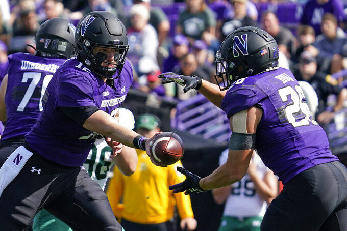 Northwestern quarterback Ryan Hilinski, left, drops off the ball to running back Evan Hull during the first half of an NCAA college football game against Ohio in Evanston, Ill., Saturday, Sept. 25, 2021. (AP Photo/Nam Y. Huh)