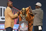 Isaac Bruce, left, a member of the Pro Football Hall of Fame Centennial Class, unveils his bust with his presenter, Sam Bruce, during the induction ceremony at the Pro Football Hall of Fame, Saturday, Aug. 7, 2021, in Canton, Ohio. (AP Photo/David Richard)