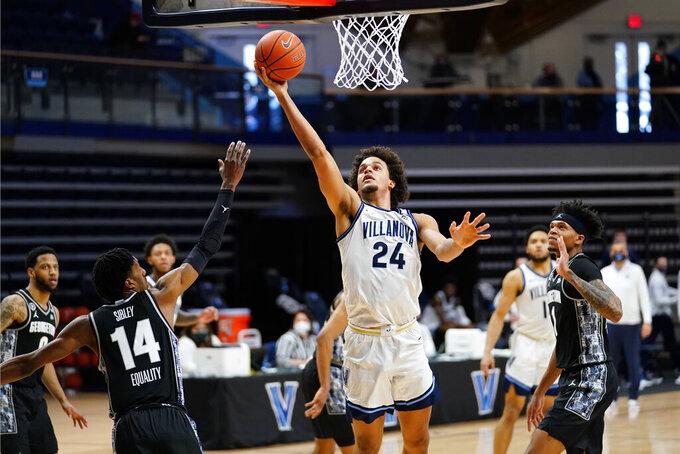 Villanova's Jeremiah Robinson-Earl (24) goes up for a shot against Georgetown's Jamari Sibley (14) during the first half of an NCAA college basketball game, Sunday, Feb. 7, 2021, in Villanova, Pa. (AP Photo/Matt Slocum)