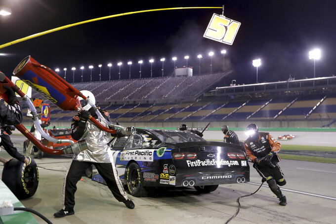 The pit crew works on Jeremy Clements' car during a NASCAR Xfinity Series auto race Friday, July 10, 2020, in Sparta, Ky. (AP Photo/Mark Humphrey)